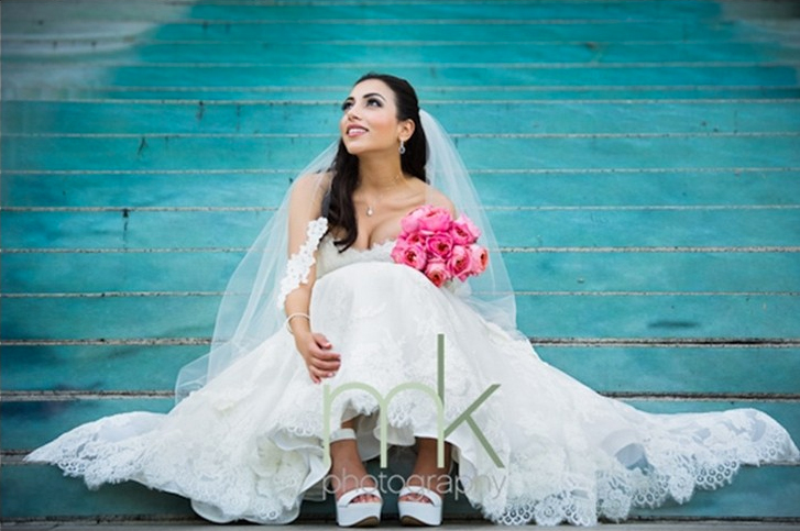 Bride holding a bouquet of bright pink flowers, sitting on blue steps.